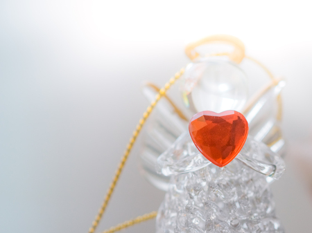 Two small glass angel statuettes with hearts