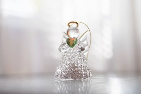 Small glass angel with a green heart in hands stands on a bright table in the center.