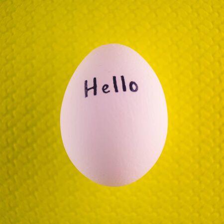 Białe jajko kurze z czarnym napisem cześć na żółtym tle