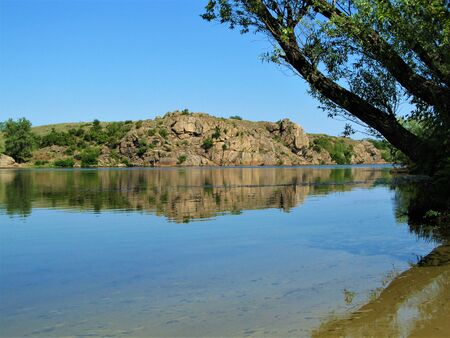 river landscape in summer, a tree over calm water with reflection of rocks on the other side Reklamní fotografie