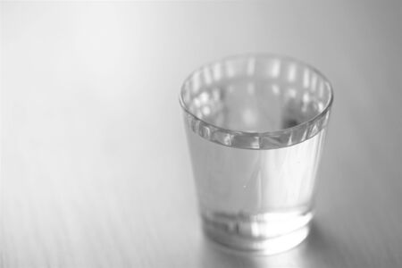 shiny glass full of water on the table, selective art focus, bw photo, copy space Banco de Imagens
