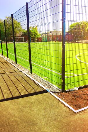 road and lawn field for playing minifootball behind the green fence mesh. Archivio Fotografico - 129443953