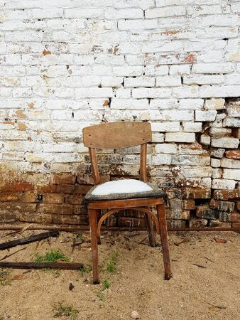 old wooden chair standing near the brick wall of a ruined house