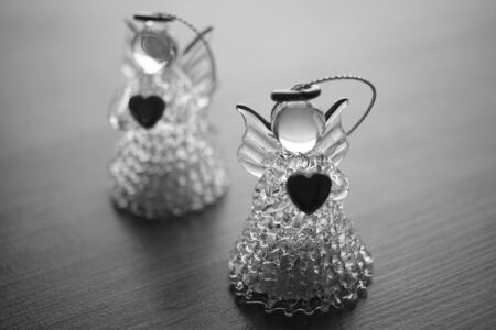 two small statues of angels on the table, black and white photo