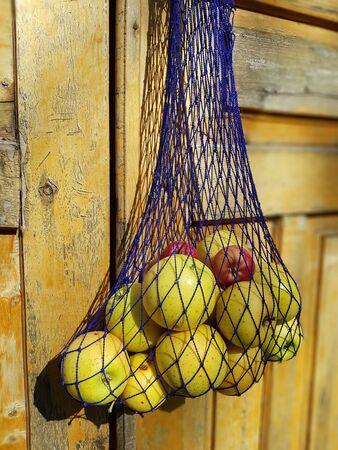 ripe apples in a blue net bag hang on the door, selective focus
