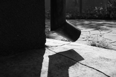 Drainpipe on the corner of the building, bright sunlight and shadow from the drainpipe on the stone floor with cracks, bw photo.