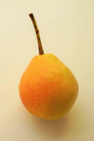 gelb-orange reife Birne auf hellem Hintergrund, weicher selektiver Fokus. Standard-Bild