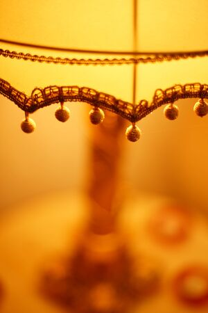 Fabric lampshade with golden balls and warm light. Close-up, selective focus