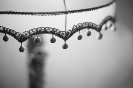 Fabric lampshade with knitted balls. Close-up, selective focus. Black and white photo