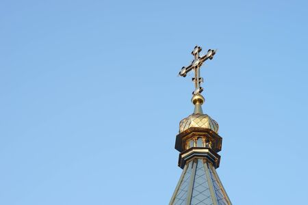 the upper part of the roof of the Orthodox Church with a cross against a blue cloudless sky