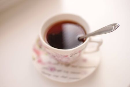 Spoon in a cup of drink. Cup of tea on a saucer in blur on a white table