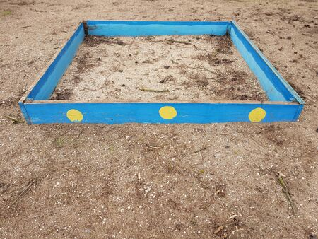 old blue wooden sandbox in abandoned kindergarten with dirty sand Stock Photo
