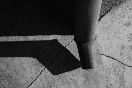 Downpipe at the corner of the building. Cracks on the stone floor. Bright sunlight and shadow from the drain pipe. Black and white photo