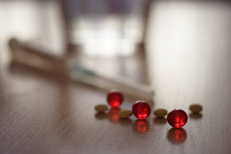 Pills and red vitamins. Syringe and water glass in blurred background. Treatment and recovery, diet or drug dependence
