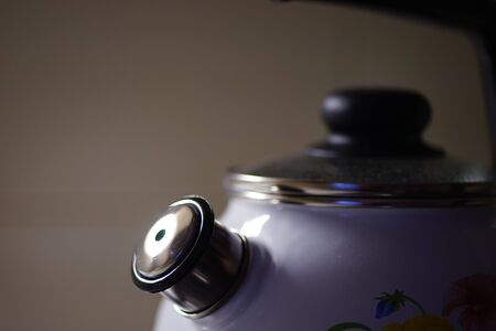 White kettle with chrome whistle, close-up in the kitchen