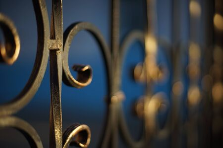 black with gilded patina forged fence with curls, selective focus, perspective view