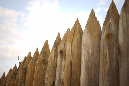Fence made of sharp wooden stakes under blue sky.