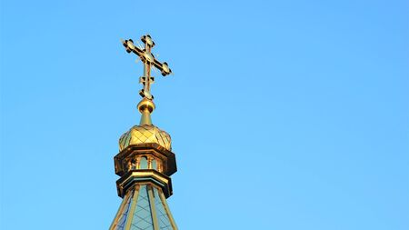 Roof top of the Orthodox Church with a cross against a blue sky. Copy space