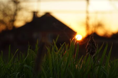 Round sun at sunset against the background of the silhouette of a village house 版權商用圖片