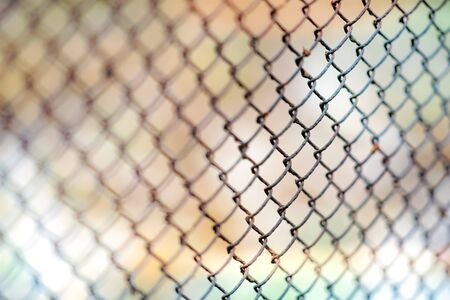 Old rusty mesh fence. Blurred colorful background. Selective focus