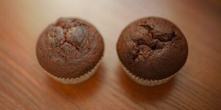 two chocolate muffins on the brown wooden table