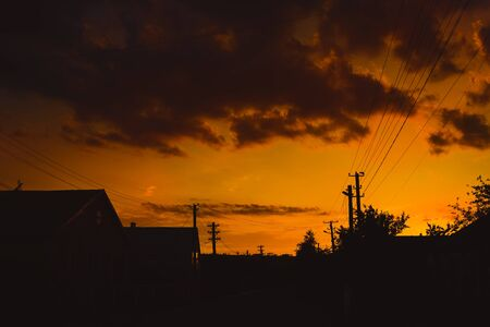 Silhouette of power lines and houses under orange sunset sky with clouds