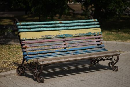 Bench with multi-colored peeling paint in the autumn sunny park