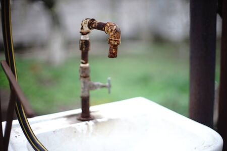 Old rusty tap on the sink in a rural yard.