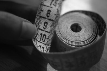 Measuring tape on the human fingers. Black and white photo.