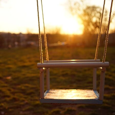 Children's swing fixed on the ropes against the backdrop of the setting sun Stockfoto