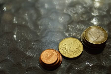 A stacks of shiny euro coins on a glass table. Imagens