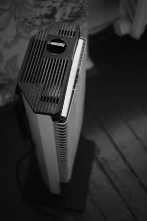 Retro electric heater Ugolek in the room, bw photo Imagens