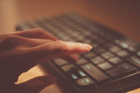female hand is typing on the keyboard, selective focus on the finger
