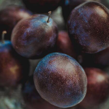 Ripe purple plums in a silver plate closeup