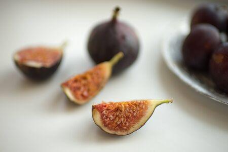 Fig slices and whole figs lie on a white table