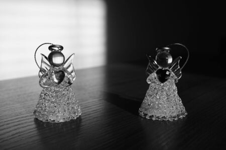 Two small statues of angels on the table, light with shadow, black and white photo