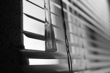 Horizontal metal jalousie, wand and rope. Background blinds. Black and white photo Imagens