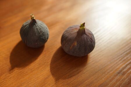 Two ripe sweet figs on a brown wooden table