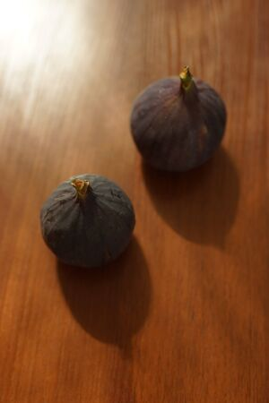 Two ripe sweet figs on a sunny brown wooden table