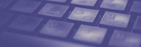 Black keyboard lit by cold blue light, macro photo