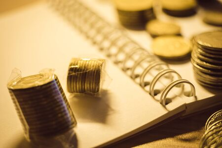 Collection of golden metal money on the notebook paper