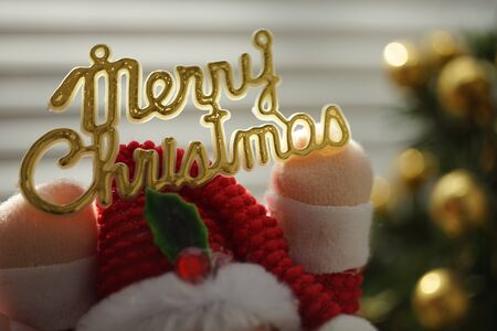 Golden text Mery Christmas in toy Santa Claus hands