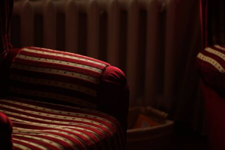 Red golden striped armchairs on a background of a heating battery in a dark room