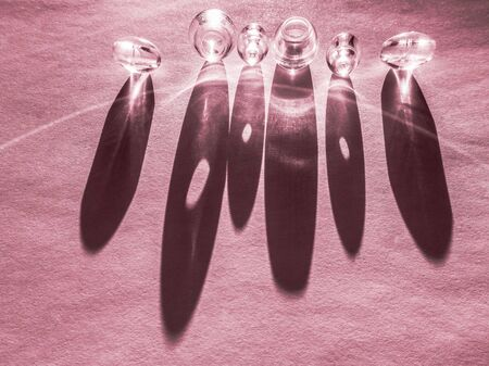 Round glass buttons on a pink paper table, hard light and shadow