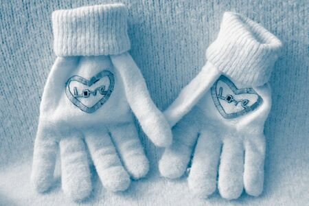 A pair of knitted gloves with love inscription, like two lovers, who hold hands, blue tone Imagens