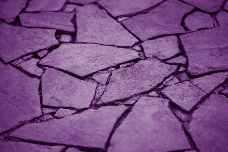 Road surface made of natural wild stones, violet tone Imagens