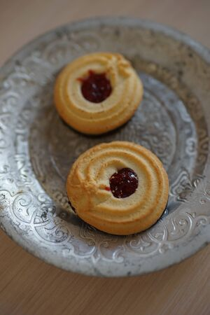 Two cookies with jam in a vintage silver plate