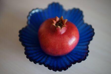 Whole ripe pomegranate on the blue crystal vase