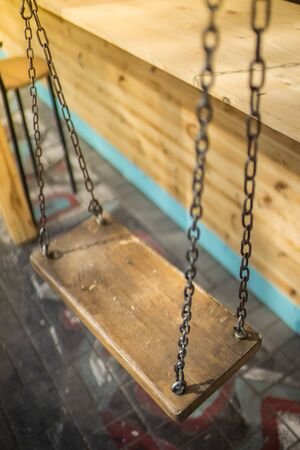 Wooden swing on a chain in a summer cafe