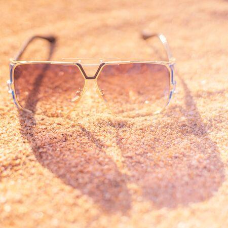 Stylish sunglasses lie on a sandy beach, transparent glass, light and shadow 스톡 콘텐츠